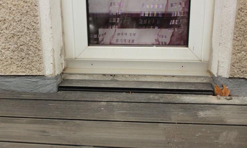 Instandsetzung einer Balkonabdichtung mit Flüssigkunststoff, nicht ausreichend hochgeführt, Balkontüren ausgespart, der Belag aus Holzoptikpaneelen ist neu